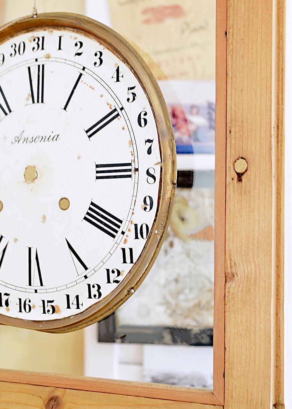 Vintage clock face on glass door on wooden vintage hutch.