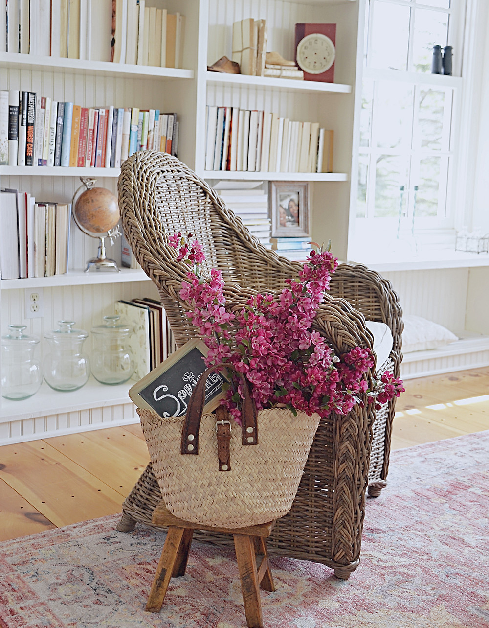 Decorated bookshelves, wicker chair flowers in a basket.
