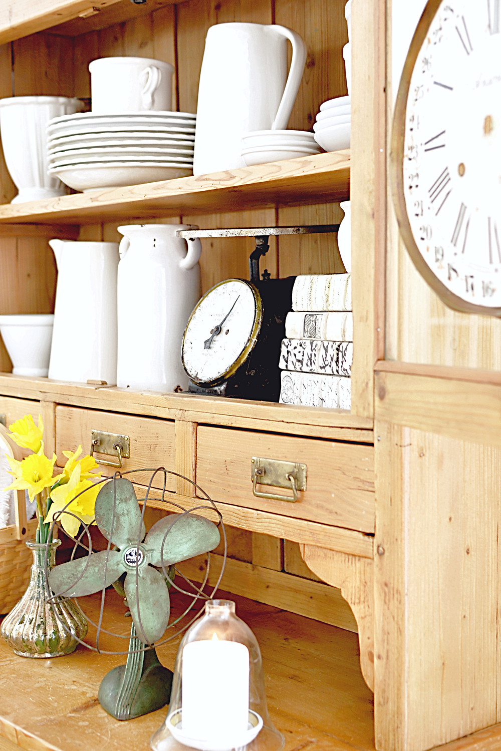 White pottery in wooden vintage hutch with vintage clock, scale, fan, candle and basket.