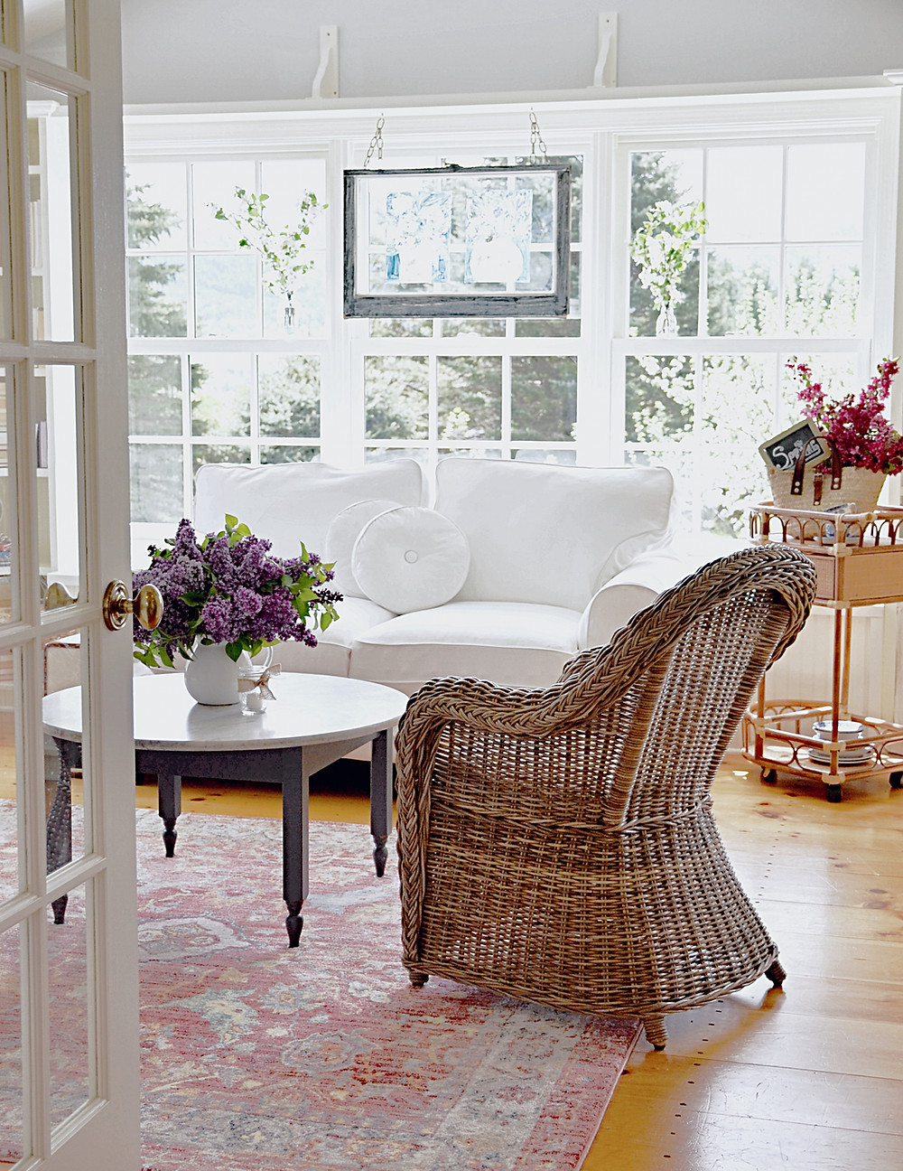 Sunroom makeover with white loveseat, vintage window hanging and a lot of flowers.