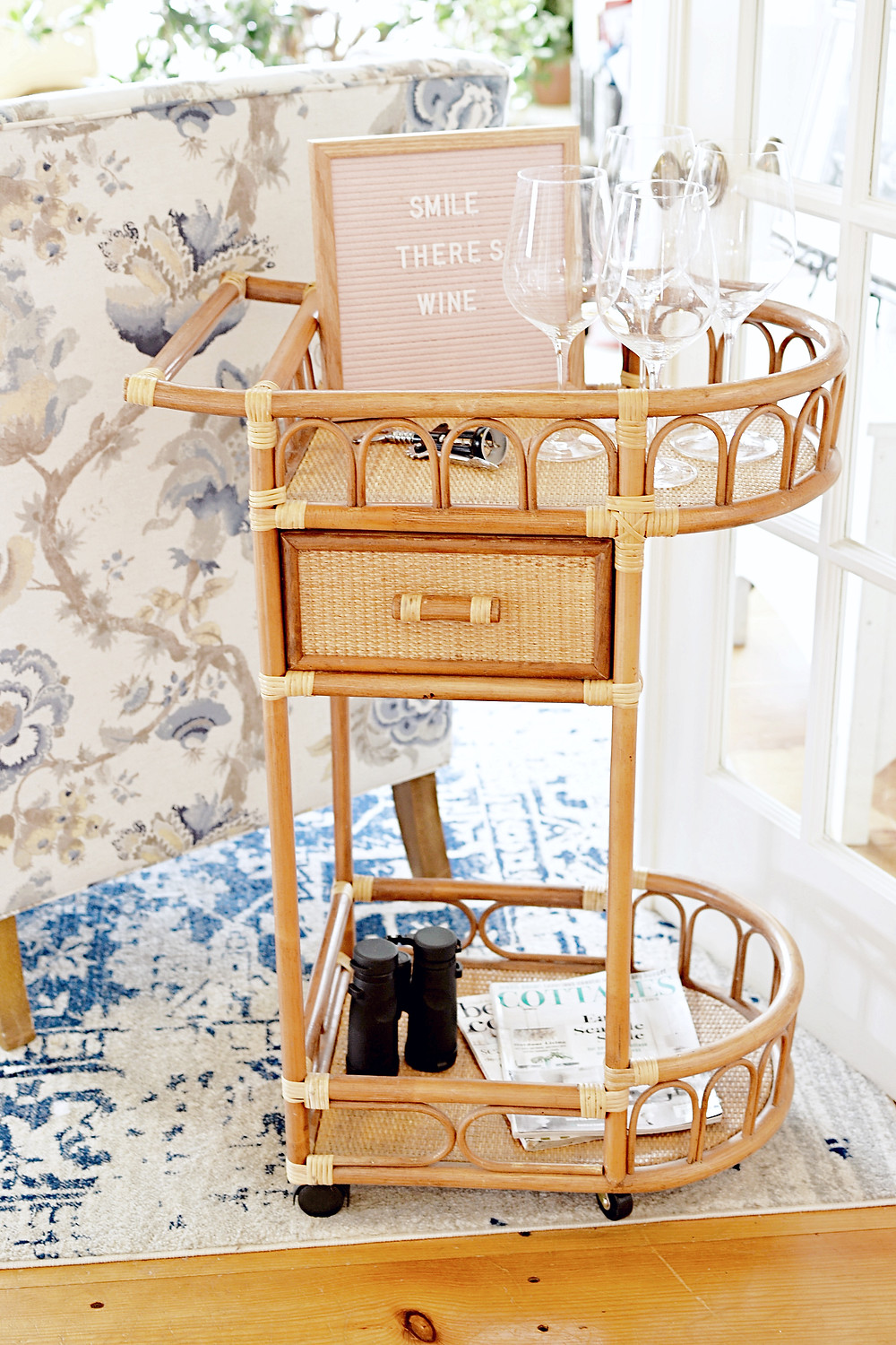 Vintage beverage cart with letter board, magazines, binoculars and wine glasses.