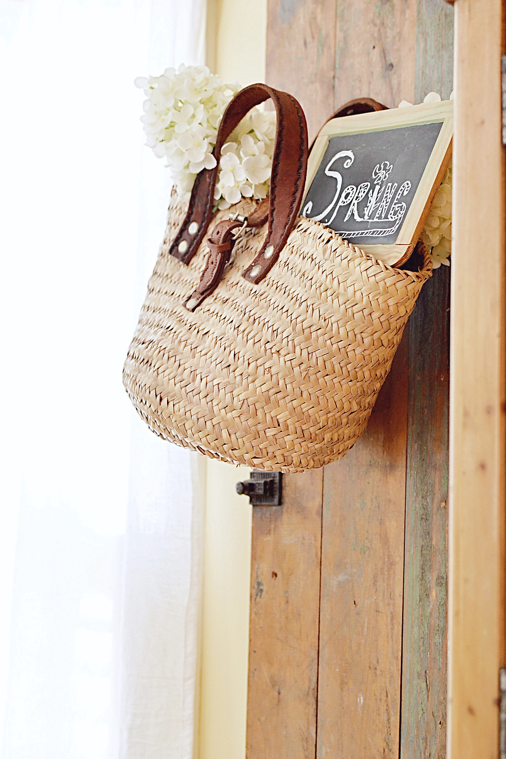 Vintage shutter with hanging basket with vintage chalkboard and white flowers for spring.