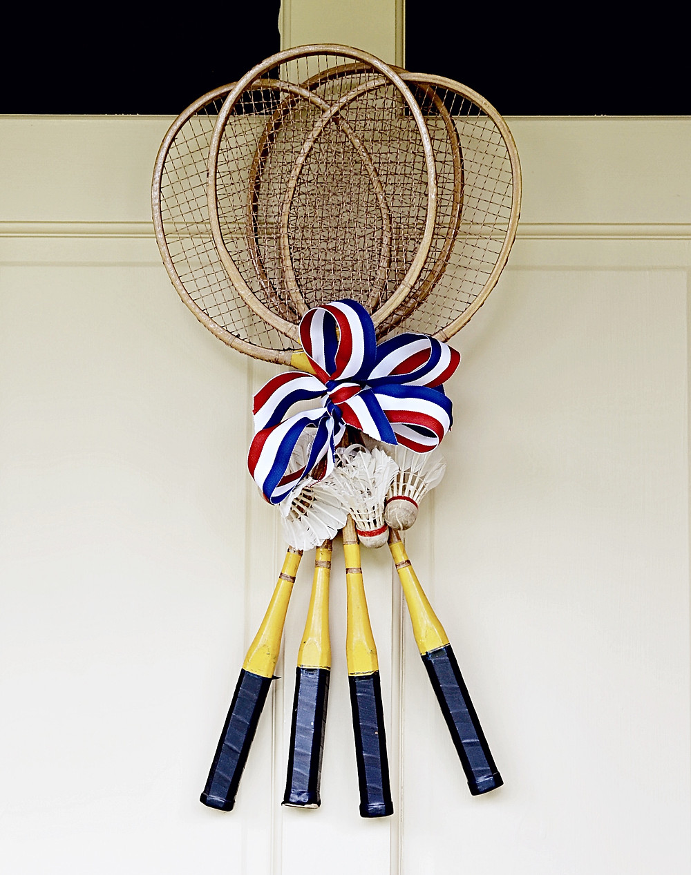 Vintage badminton racquets with vintage birdies and red, white and blue ribbon.