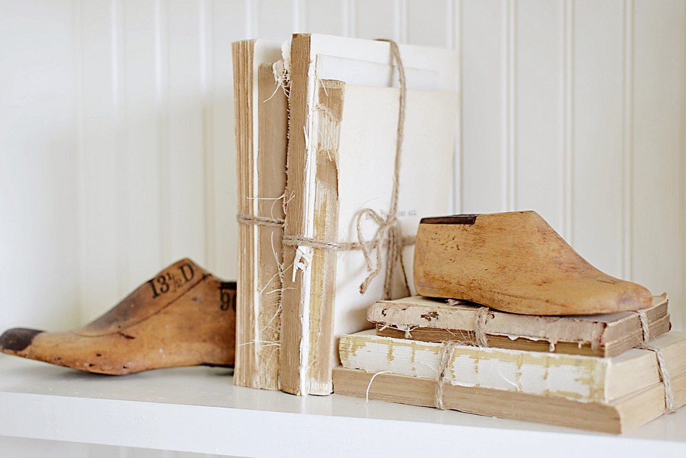 Vintage shoe stretchers and vintage books with twine on white shelf.