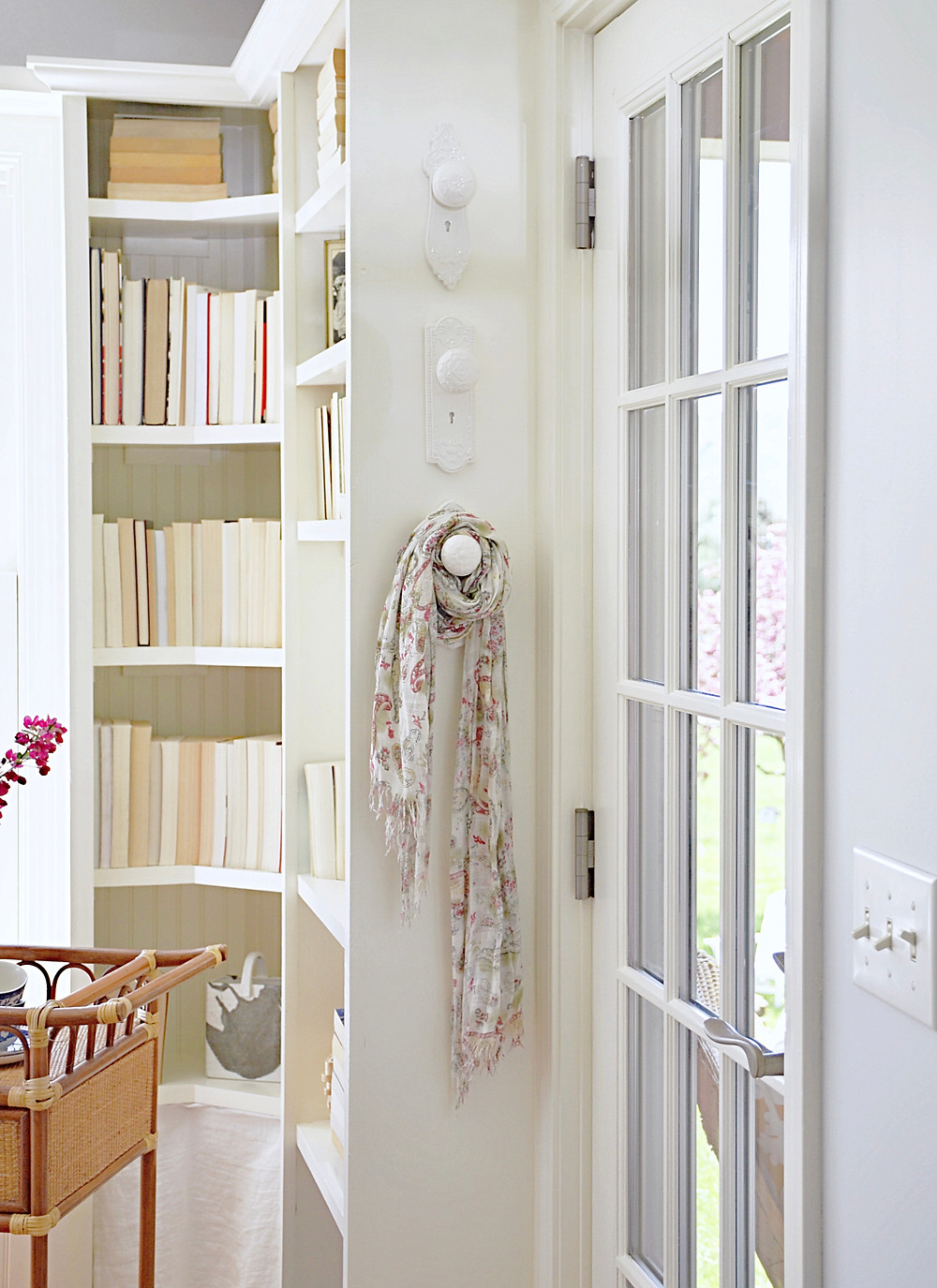 Porcelan white door knob wall hangers and bookshelves w/ books.