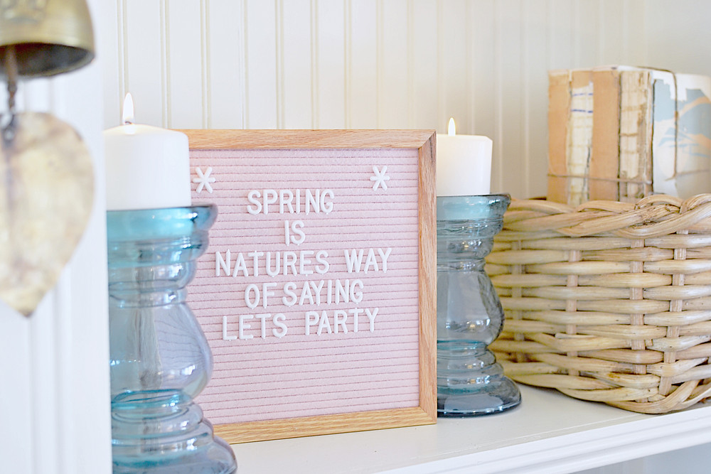 Pink felt letter board, blue candle glass candlesticks, basket, vintage books in a white built in shelving