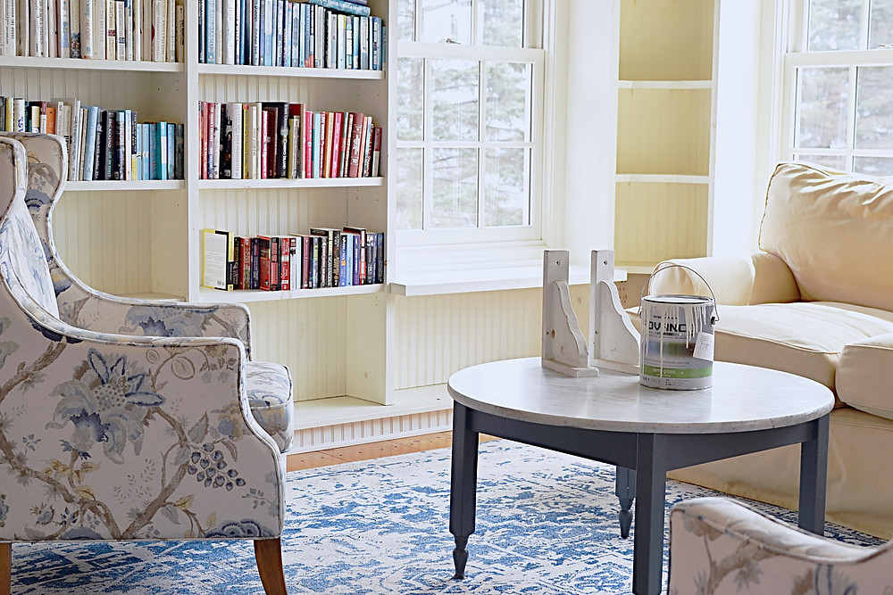 Before picture with yellow loveseat, blue chairs and rug and dingy bookshelves.