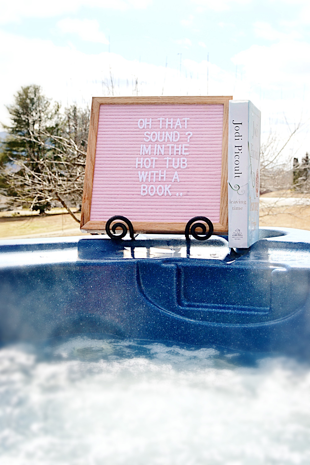 Pink felt letter board displayed on a hot tub with hardcover book.