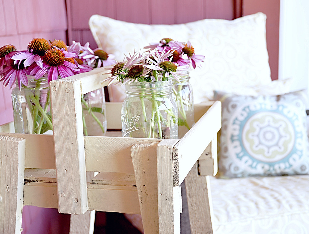 Vintage flower stand with mason jars and flowers on the porch.