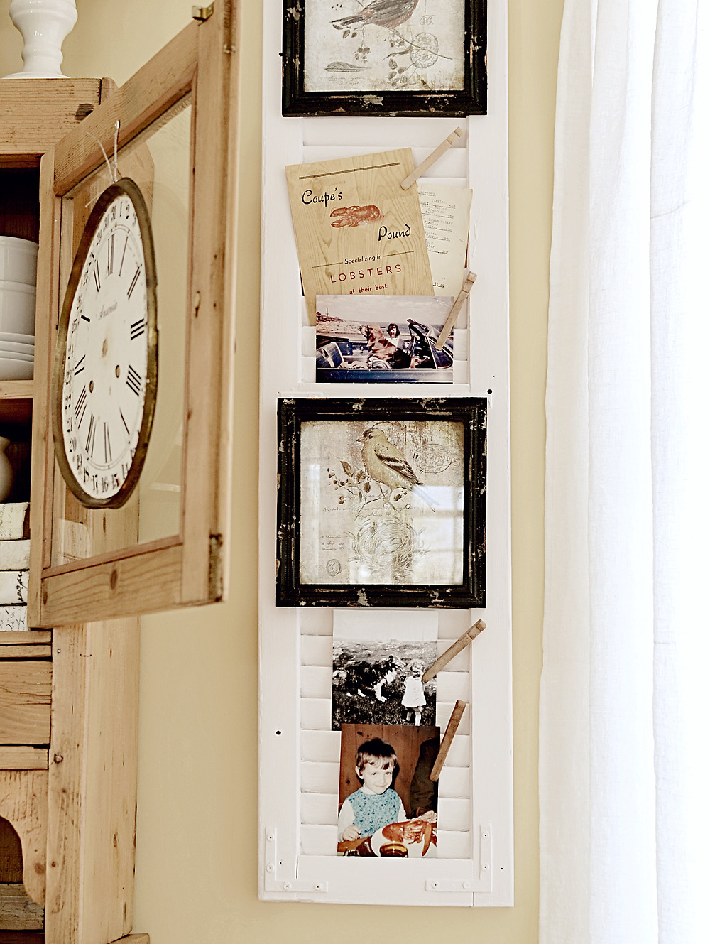 Vintage painted shutter with nostalgia and vintage family photos next to vintage clock face on vintage dining hutch.
