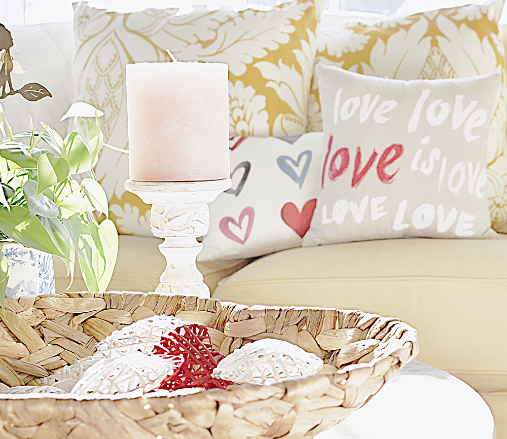 Valentine's Day decor with pillows, candles and heart basket.