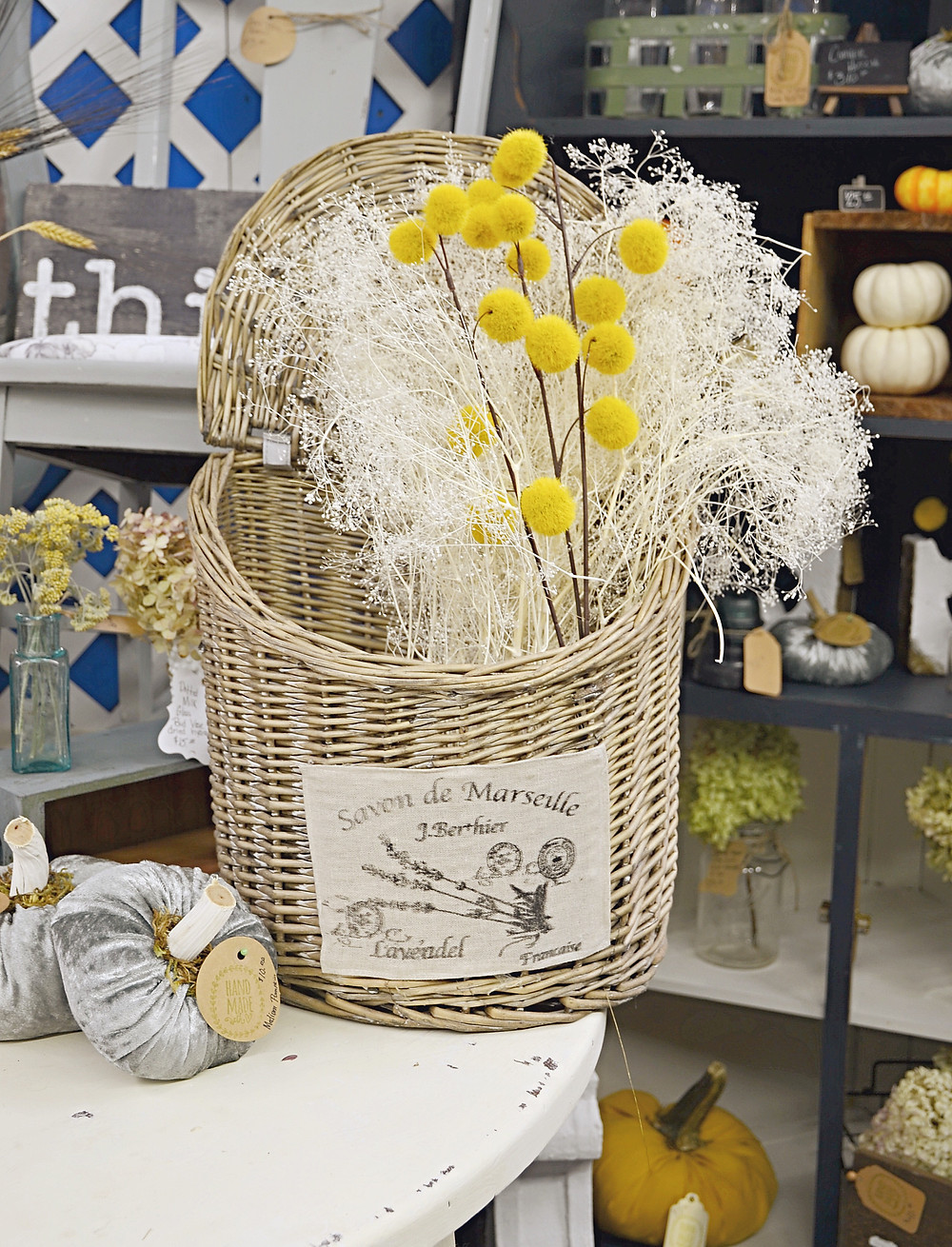 Vintage basket full of white and gold dried flowers.