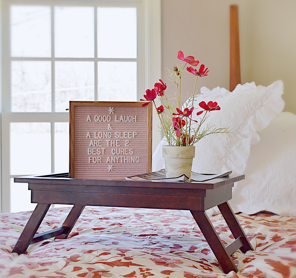 pink felt letter board, breakfast tray, flowers on a high vintage bed with white pillows in the guest bedroom.
