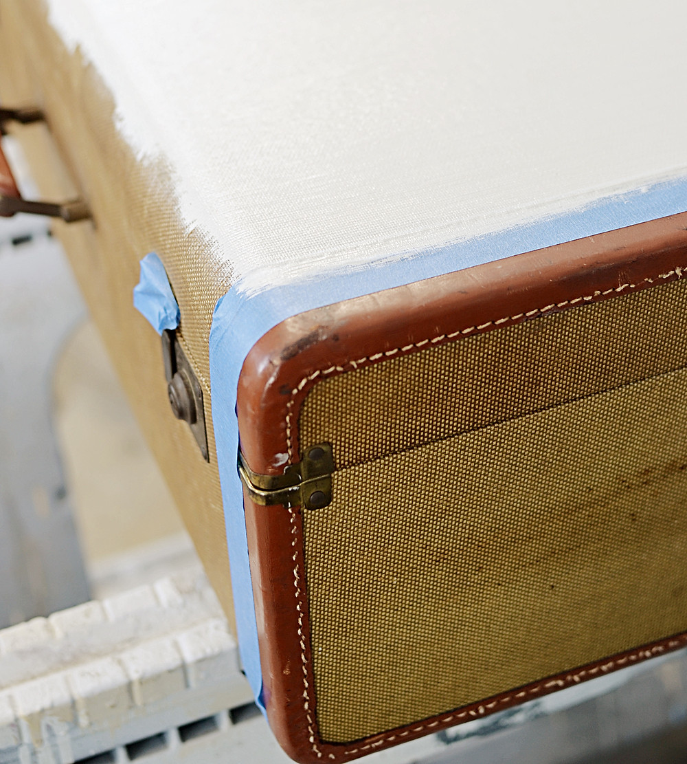 Vintage suitcase with white paint and blue painters tape