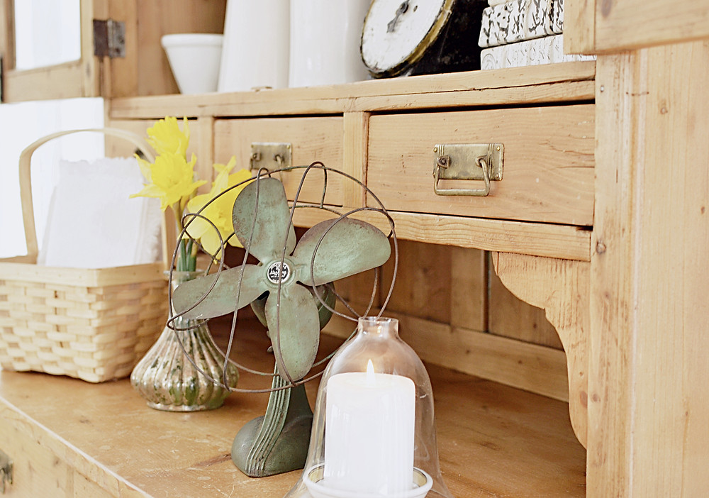 Vintage green fan, daffodils, basket, candle, scale, books and whites in an old wooden hutch.