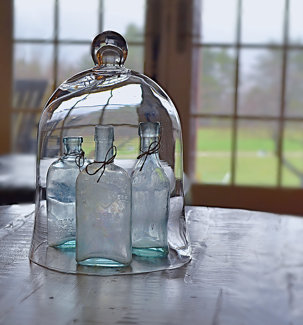 Cloche with blue vintage bottles.