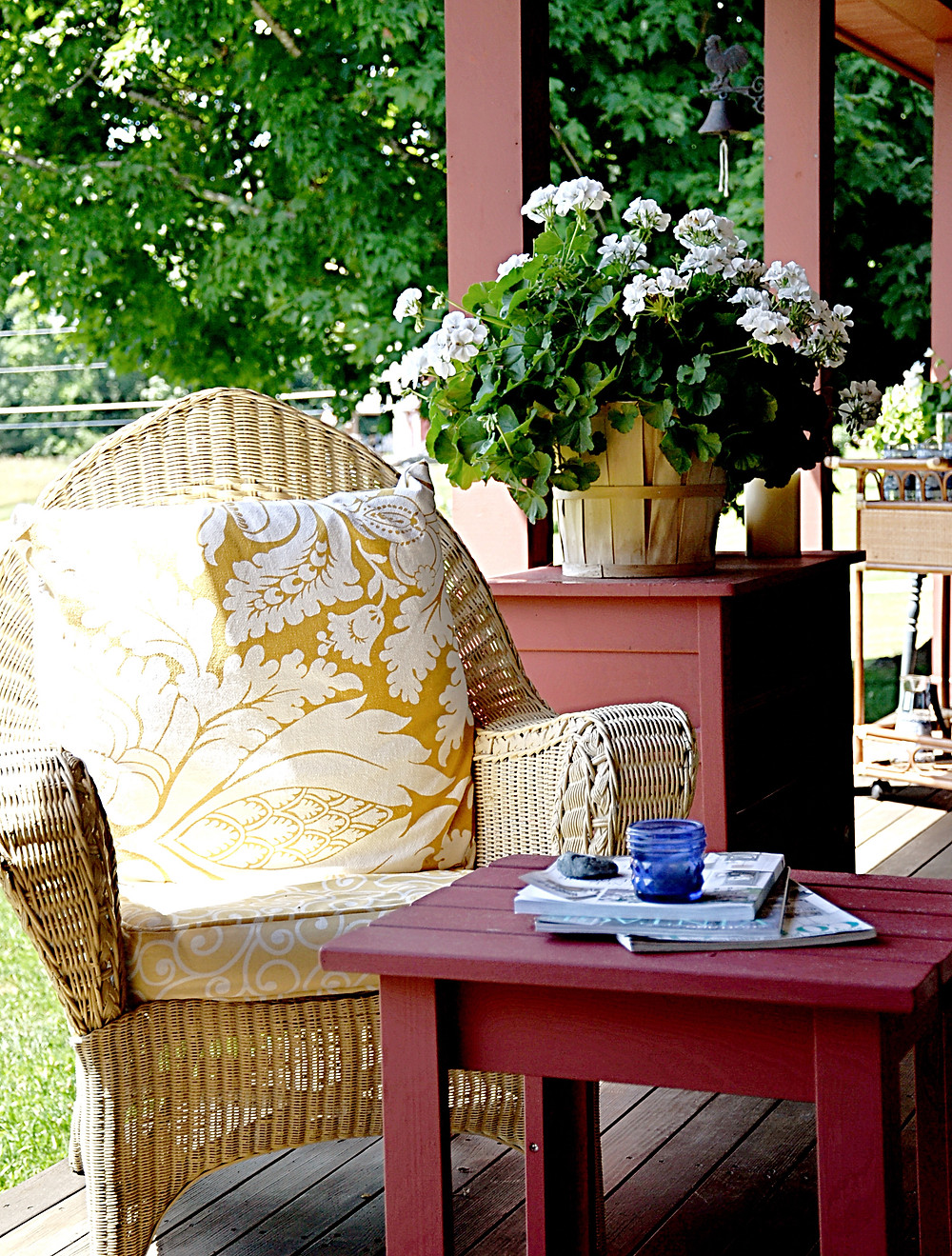 Wicker chair with magazines and flowers on the porch.