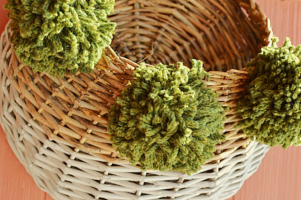 Basket with green pom poms outside