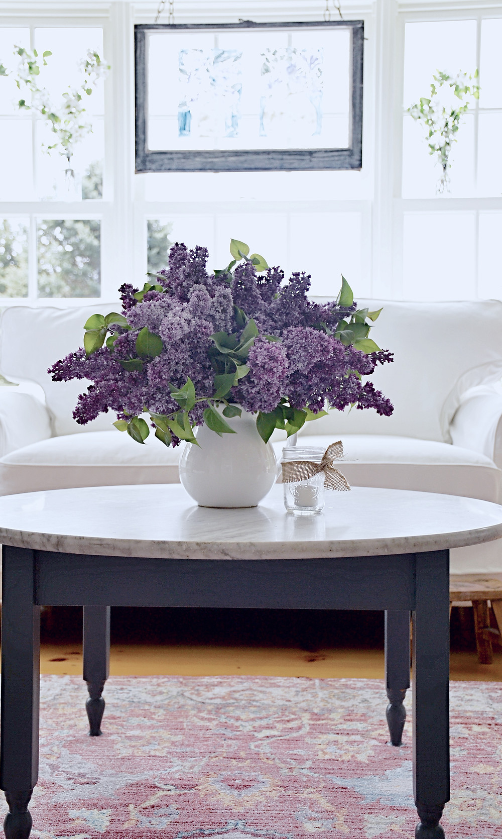 Sunroom makeover with white loveseat and lilacs on coffee table.