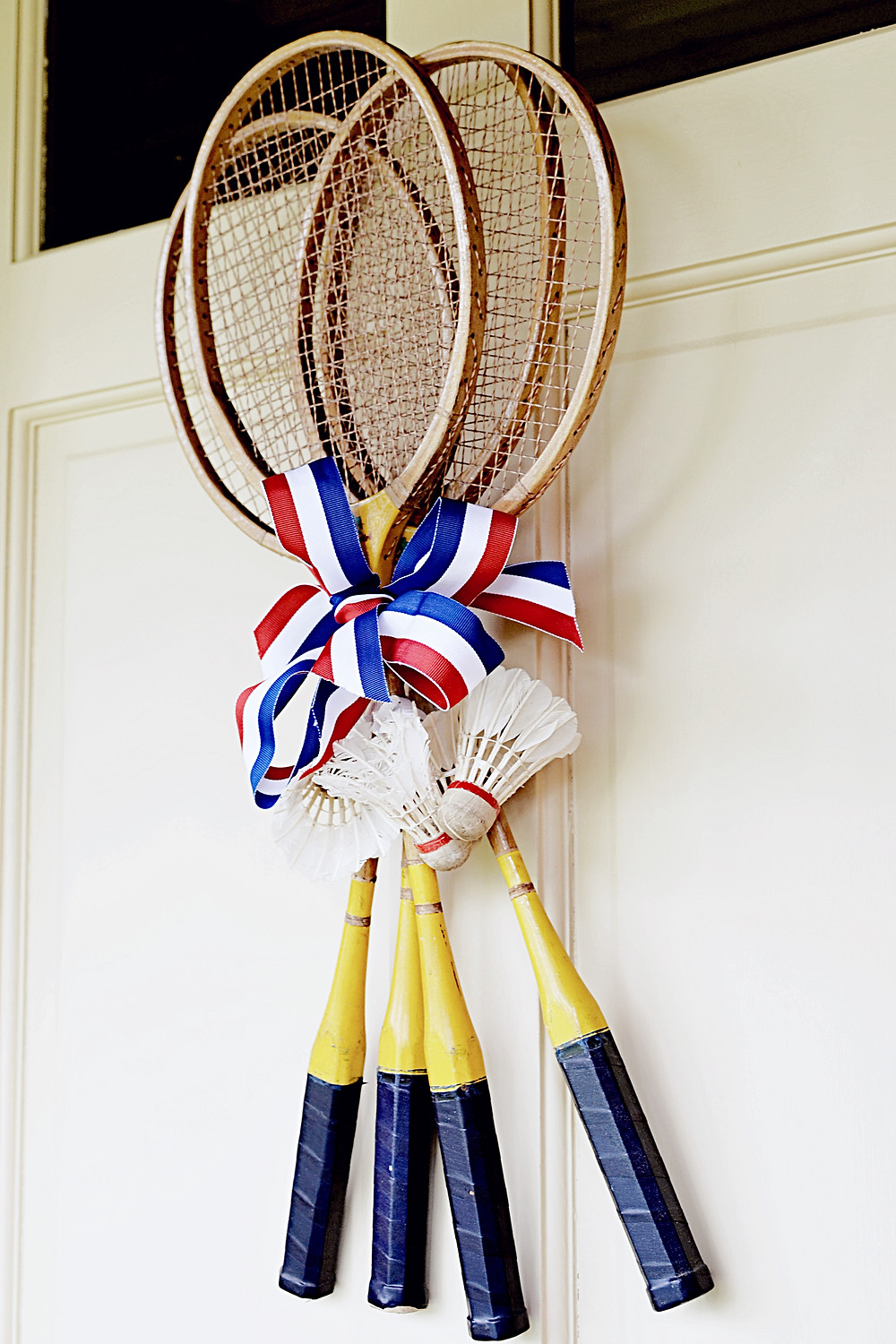 Vintage badminton rackets w/ vintage birdies and red, white and blue ribbon.