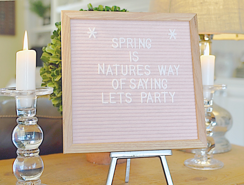 Pink felt letter board, glass candle sticks, silver lamps on wooden couch table.