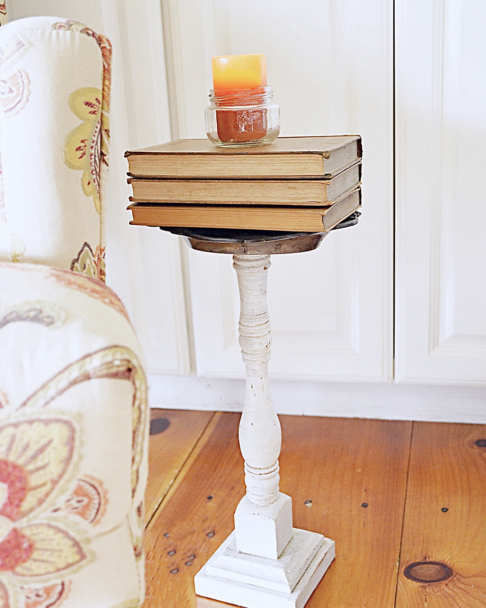 Vintage books with orange candle in jar for fall decor.