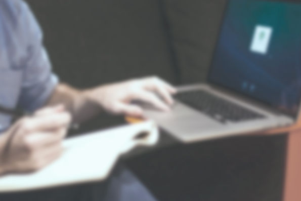 blurred out of focus worker entering information into a computer