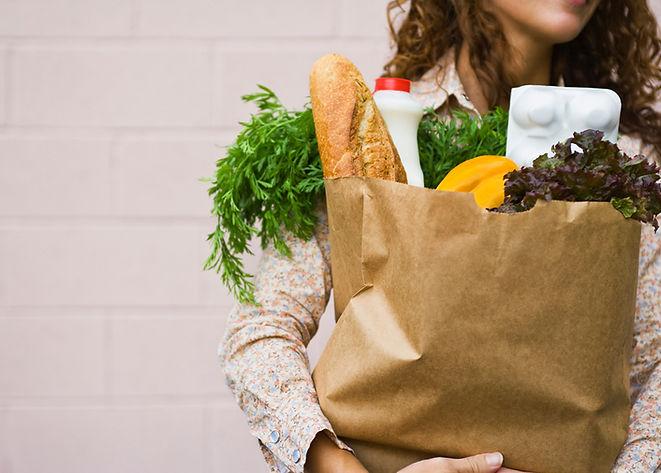 femme tenant un sac d'épicerie