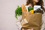 Lady is carying grocery in the paper bag. Baguette, vegetable, herbs.