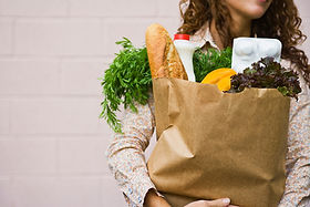 woman holding grocery bag full of food