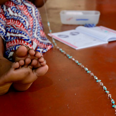 A participant stringing beads