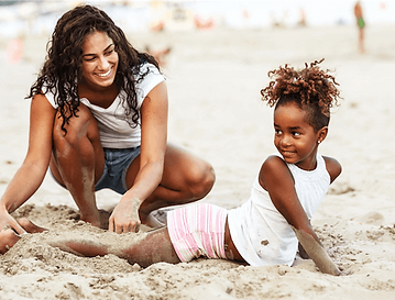 Mother with genetic fibroids playing on the beach with her daughter