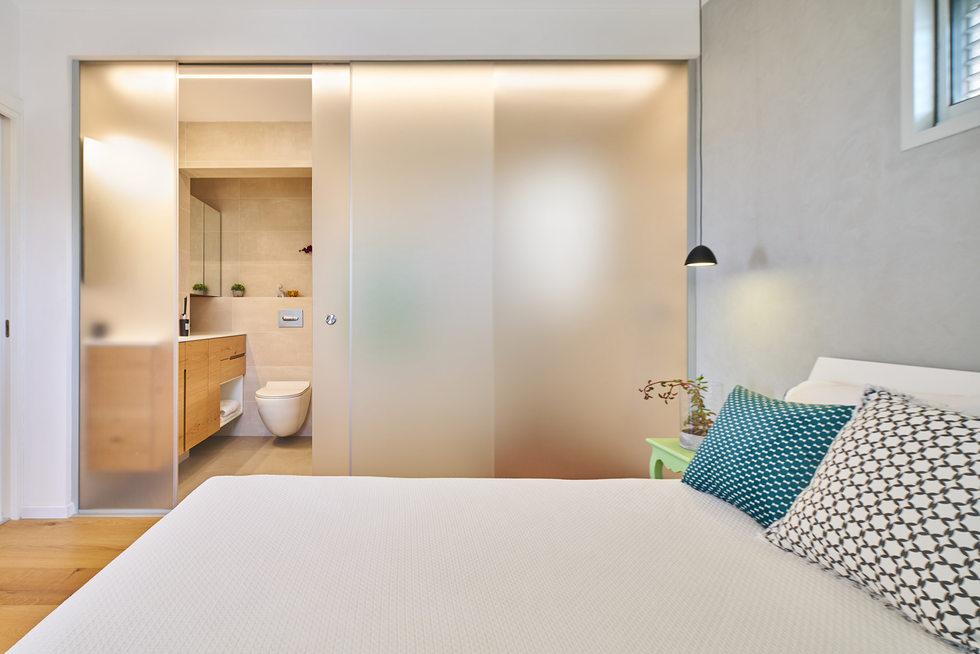 חדר שינה עם מחיצה למקלחת