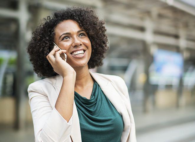 Femme noire au téléphone qui sourit dans la rue