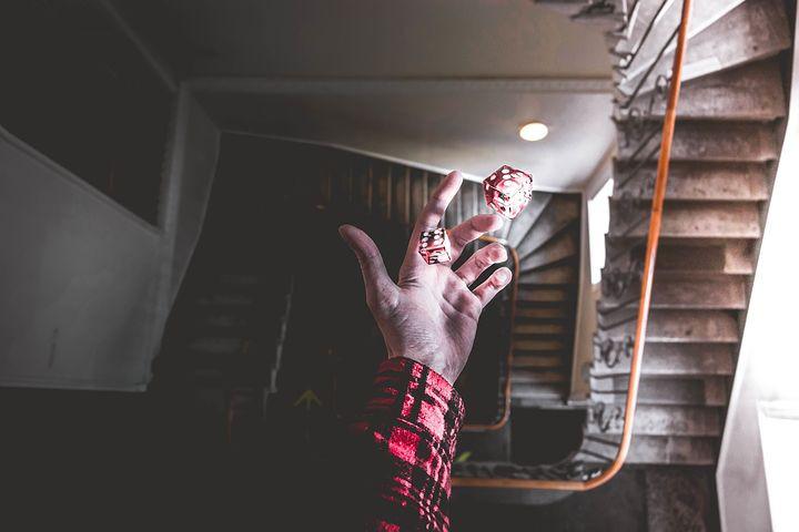 Main qui lance des dés rouges et blancs dans des escaliers