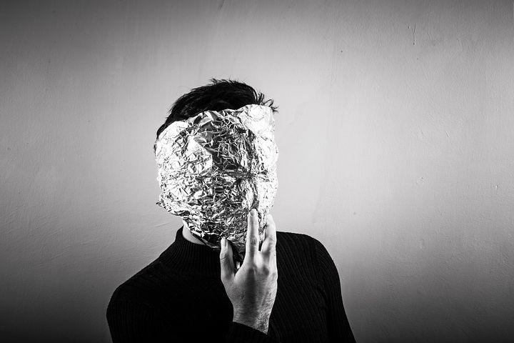 Image en noir et blanc, un homme se cache le visage avec du papier aluminium