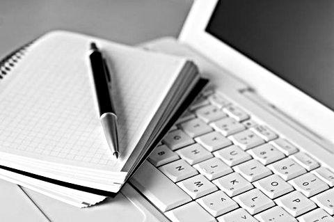 Cahier et stylo posés sur un ordinateur