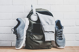 Green backpack with sportswear and sneak
