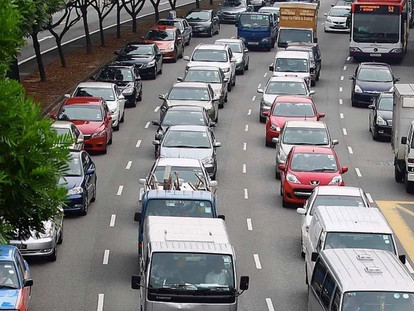 How many green cars are there on the road?
