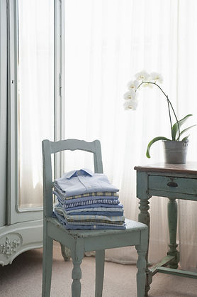 Stack of ironed shirts on wooden chair.j