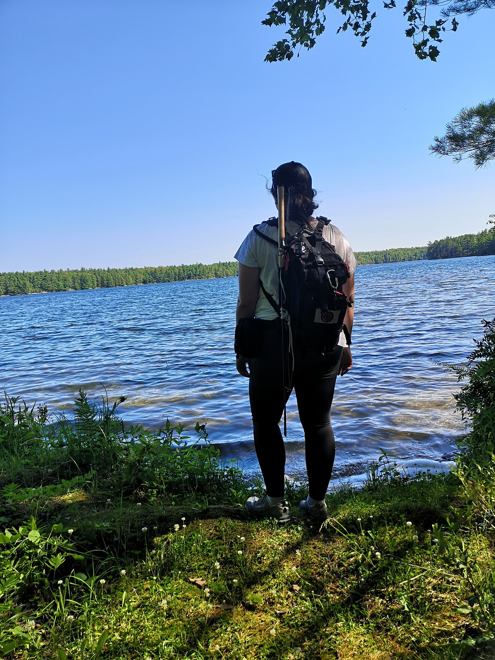 Bec standing in front of a lake with hiking bag on