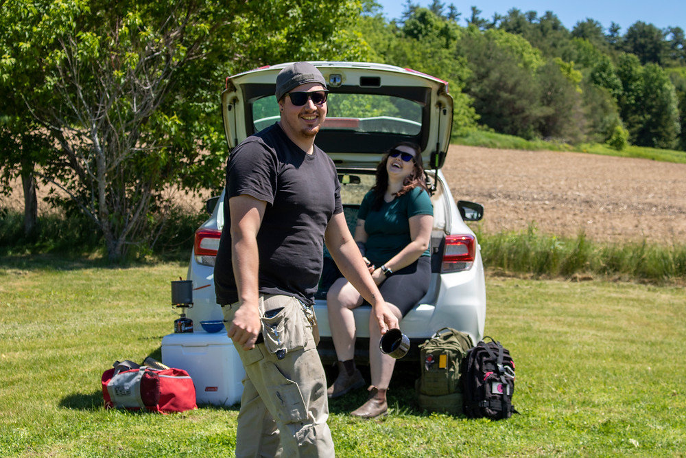 2 people laughing outside of Subaru Impreza camping