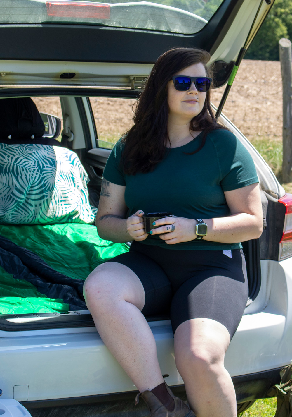 Woman sitting on the back of a Subaru Impreza drinking coffee
