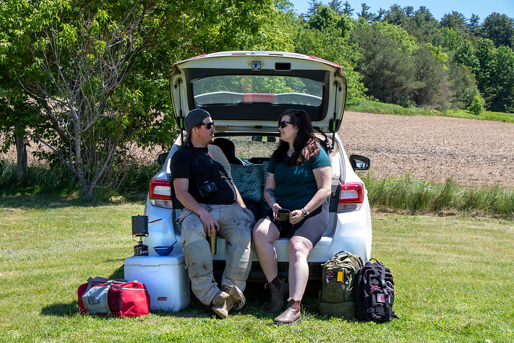 2 people sitting on the back of a Subaru Impreza