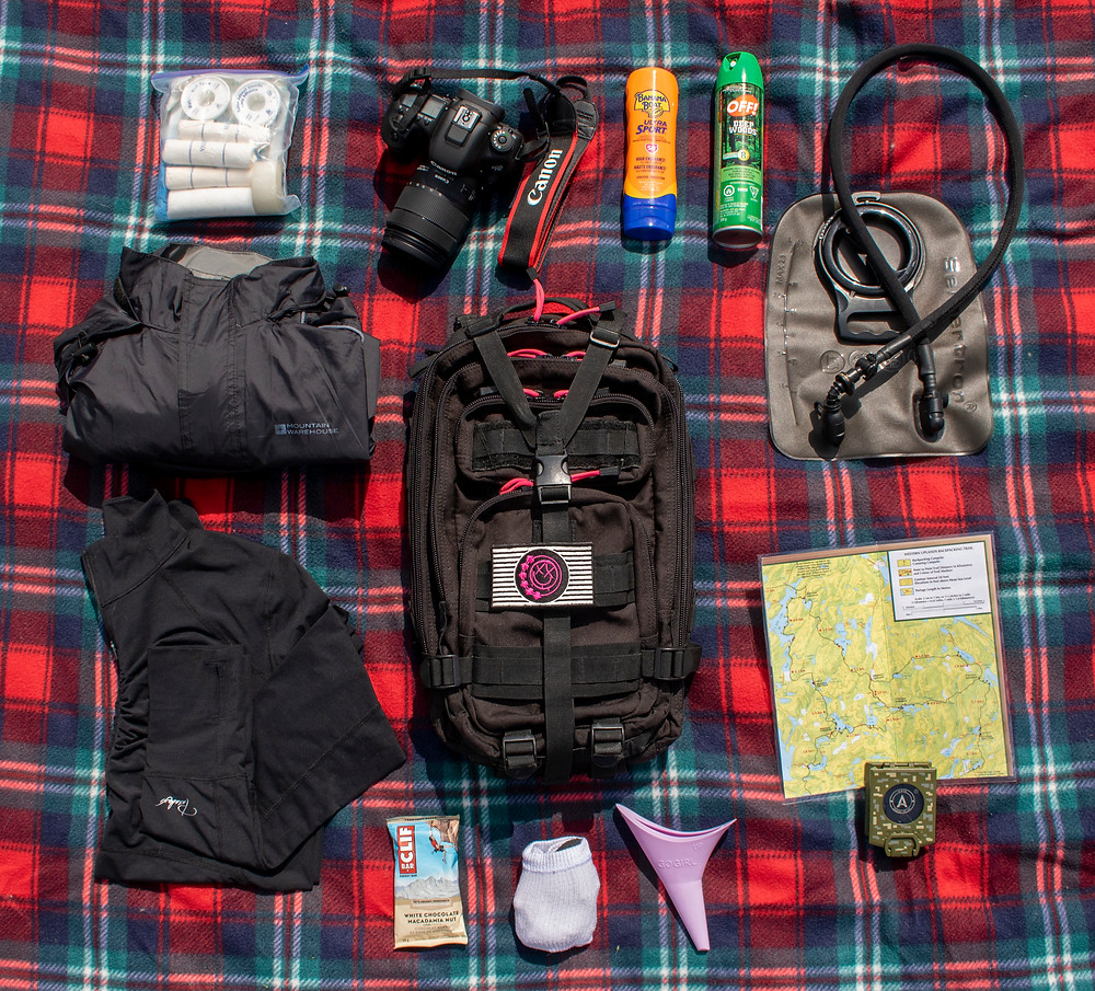 several hiking items laid out on a blanket surrounding a backpack