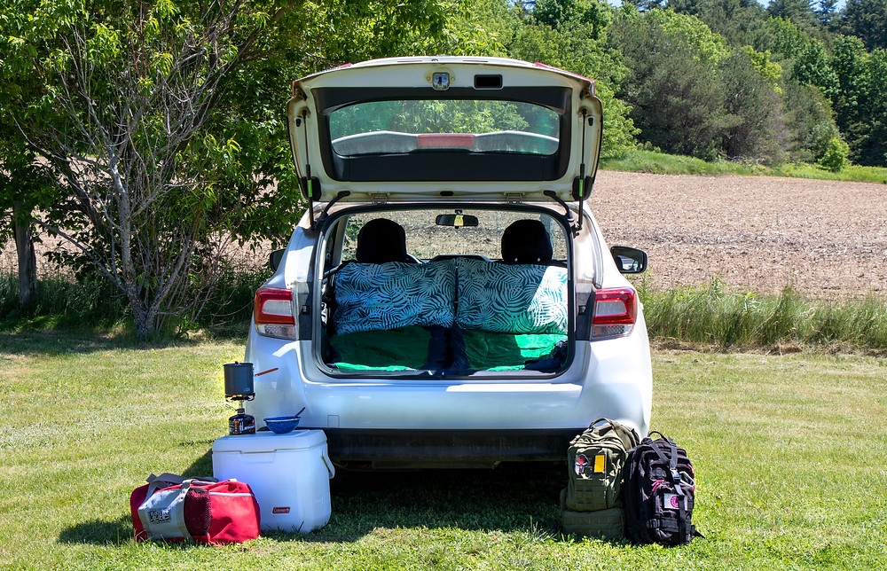 Subaru Impreza with sleeping bags and camping gear set up in and around it