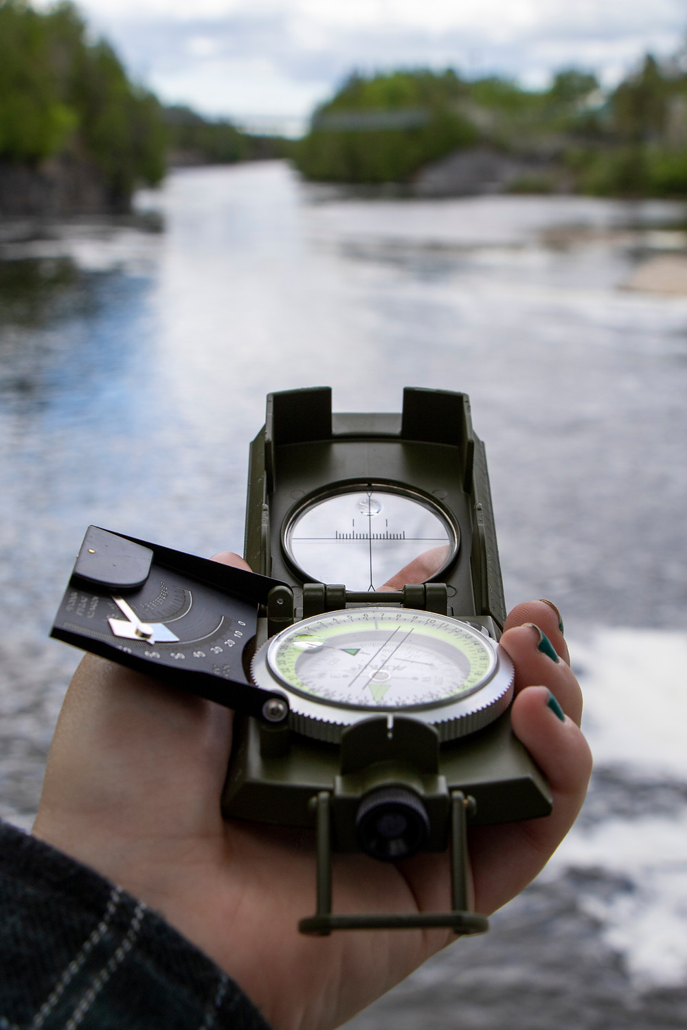 Open compass held in front of a river