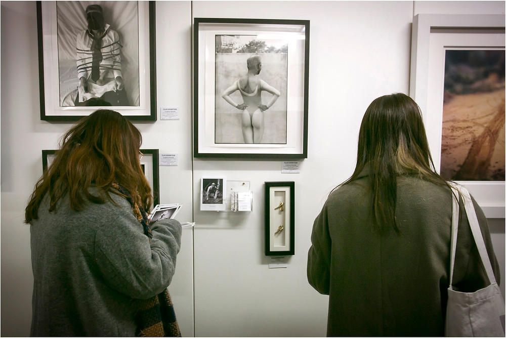 people are looking at a work of art, during an exhibition in London