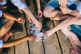 友達同士で円陣を組んでカード遊びをしている。