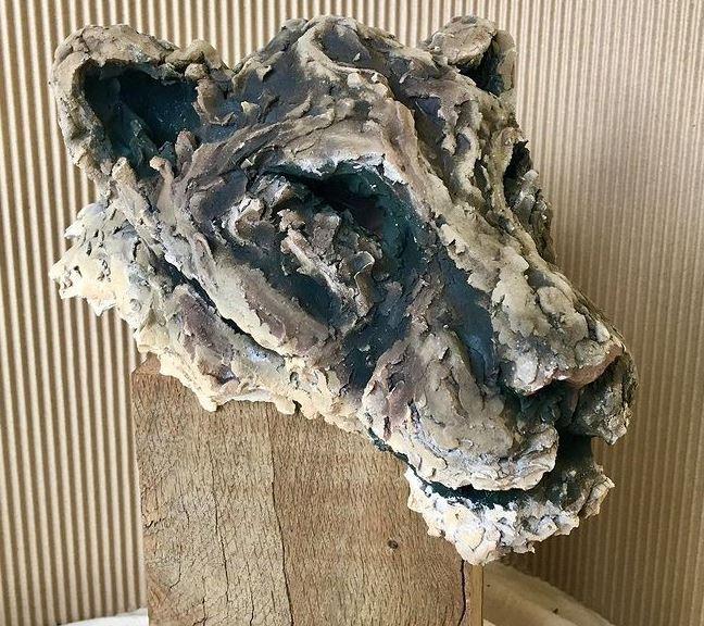 Lionne en céramique (sculpture), par Ronceval. Céramique enfumée sur socle de bois brut.
